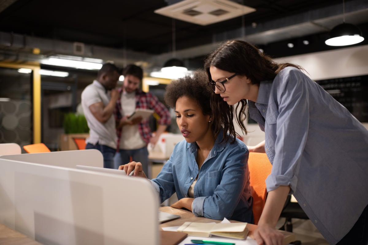 Two businesswomen reviwing information on a computer