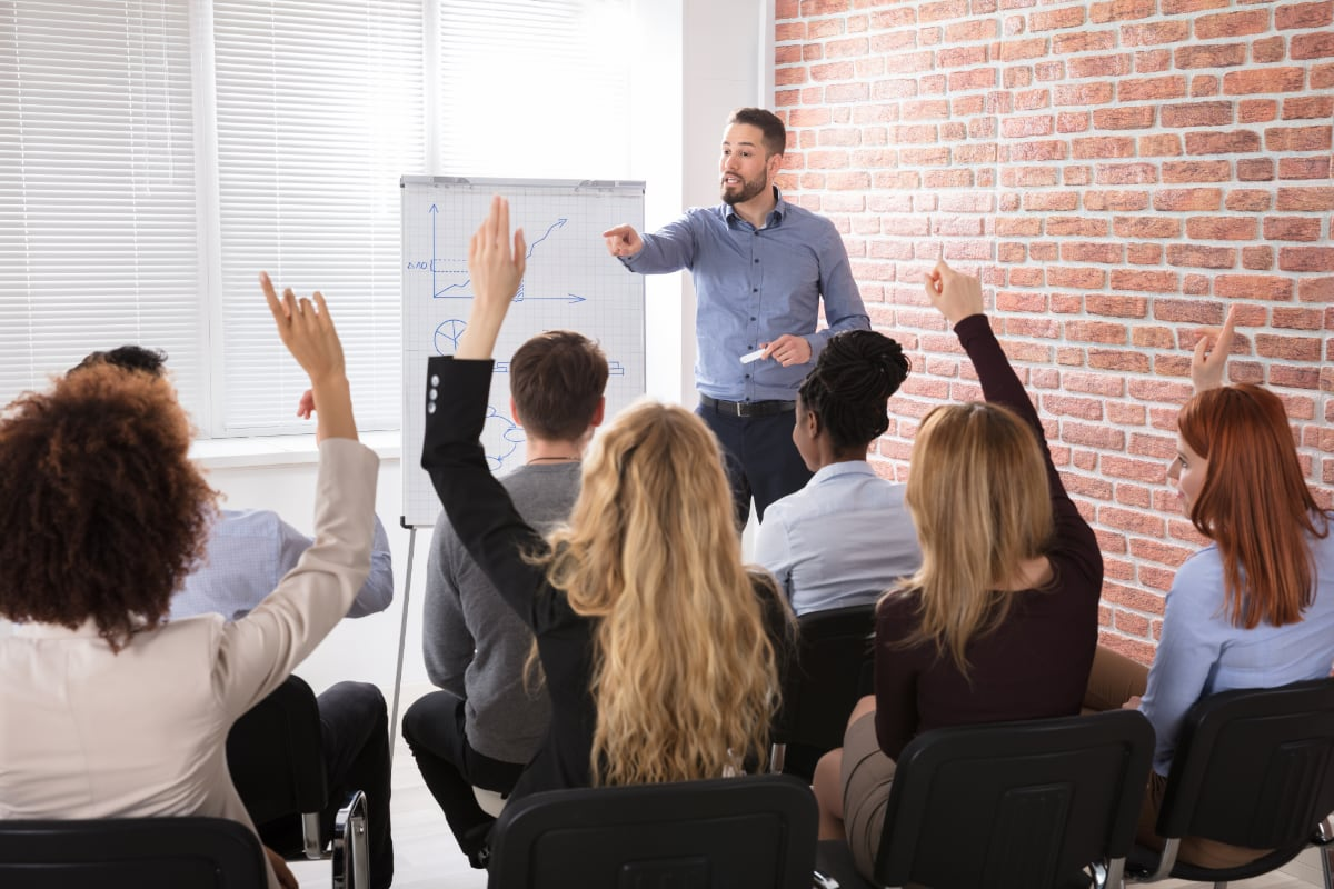 A business man with a chart taking questions from a group