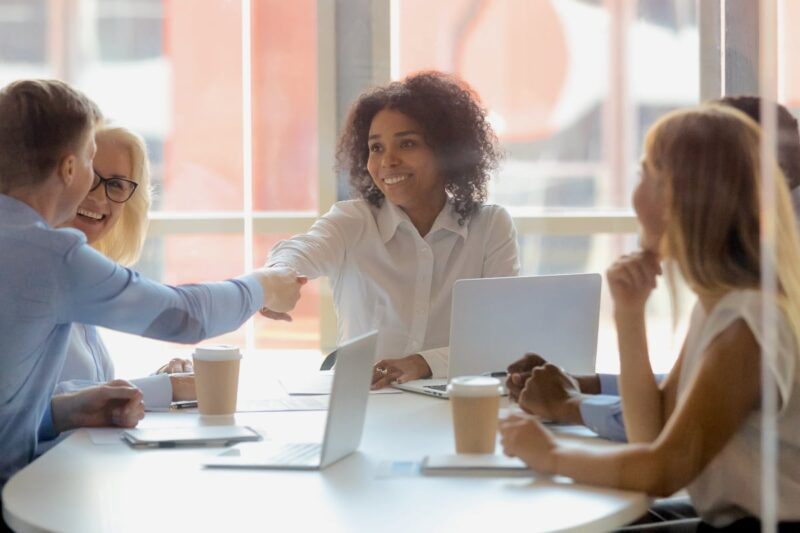 Woman shaking hand of colleague at conference table