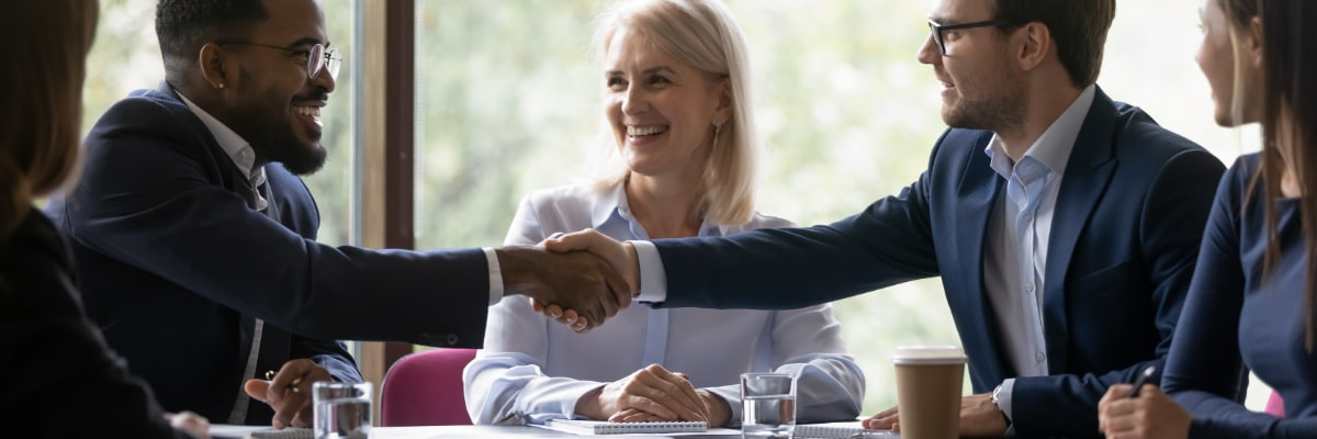 business meeting with woman at center in between two men shaking hands across table