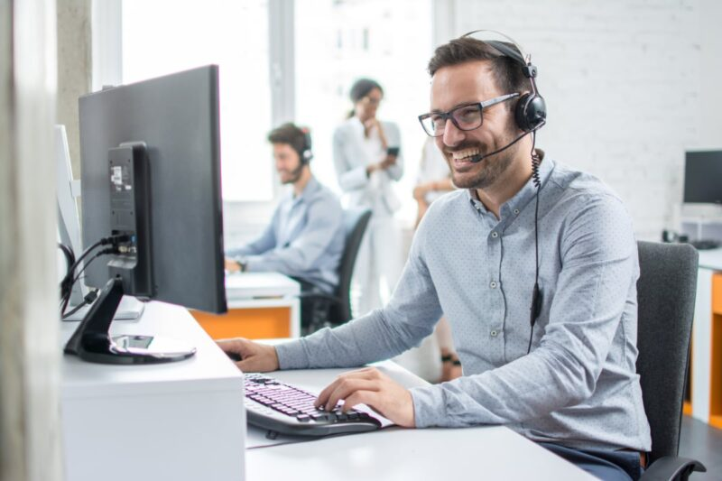 man sitting at computer with headset phone